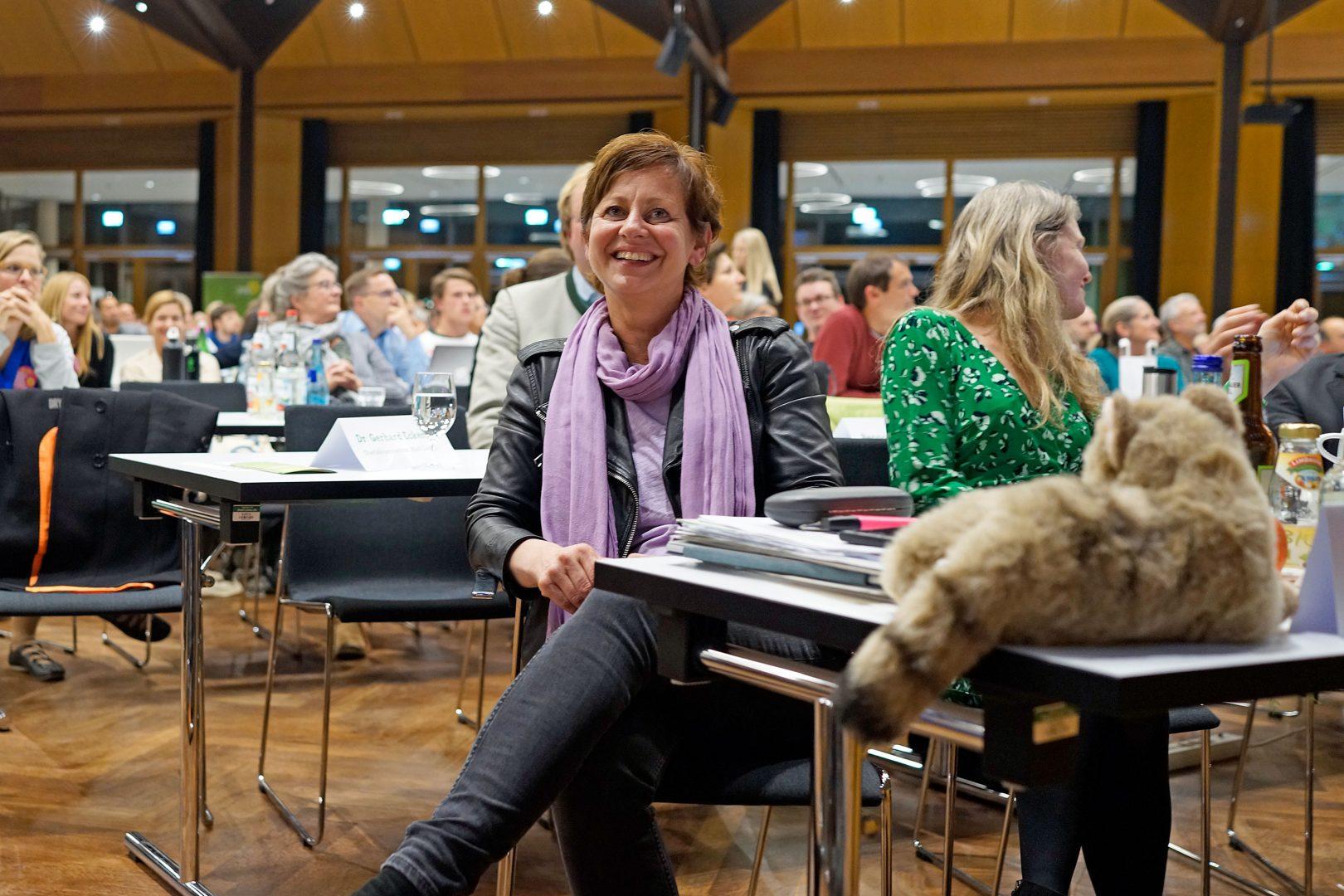 Landesvorsitzende Sigi Hagl bei Ihrer Verabschiedung: Sie sitzt auf ihrem Platz und schaut nach oben zur Bühne, wo ihr Ko-Vorsitzender Eike Hallitzky gerade die Laudatio auf sie hält.