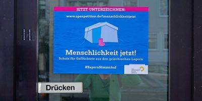 """Foto eines Plakats für die Petition """"Menschlichkeit jetzt!"""", das an der Türe eines Geschäfts klebt"""