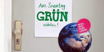 """Foto einer Wohnungstür, die beklebt ist mit einem Schild """"Am Sonntag Grün wählen"""", einem Foto der Erde aus dem All und dem pinkfarbenen Pin mit der Aufschrift """"Weil wir hier leben"""", der sich durch die ganze Kampagne der bayerischen Grünen zur Kommunalwahl zieht"""