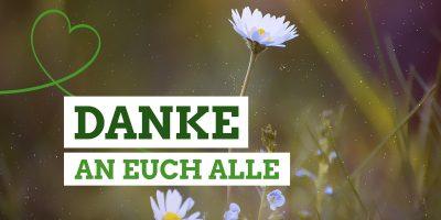 """Nahaufnahme einer Blumenwiese mit dem Text """"Danke an euch alle"""""""