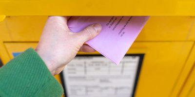 Eine Hand wirft einen roten Wahlumschlag in einen gelben Briefkasten