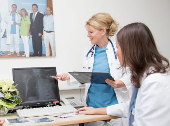 Dr. Ulrike Bechtel bei der Arbeit im Krankenhaus. Gemeinsam mit einer Kollegin analysiert sie gerade ein Röntgenbild.