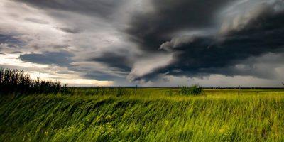 Ein Unwetter mit dunkelgrauen Wolken rollt über eine Landschaft hinweg