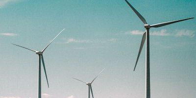 Drei Windräder vor einem blauen Himmel