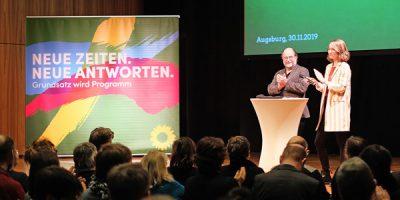 """Die grünen Landesvorsitzenden Eike Hallitzky und Eva Lettenbauer auf der Bühne bei der bayerischen Regionalkonferenz zum neuen Grundsatzprogramm. Das Motto des Prozesses ist auf einem Banner zu sehen: """"Neue Zeiten, neue Antworten"""""""