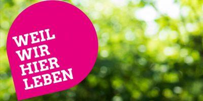 Weil wir hier leben – das Motto zur grünen Kampagne für die bayerische Kommunalwahl am 15. März 2020, gesetzt auf einem magentafarbenen Pin vor verschwommenem grünen Hintergrund