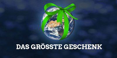 """Ansicht der Erde aus dem All, um den Erdball ist eine grüne Schleife gebunden, dazu der Text: """"Das größte Geschenk"""""""