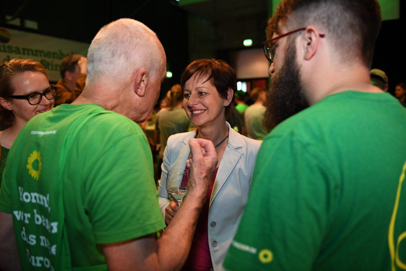 Sigi Hagl im Gespräch mit zwei grünen Helfern