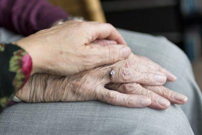 Die Hand einer jüngeren Person liegt auf der Hand einer älteren Person