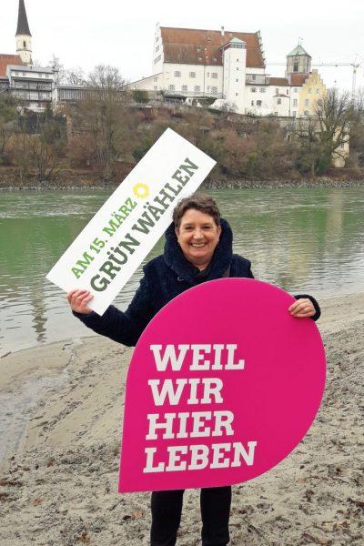 """Steffi König am Inn in Wasserburg vor der Kommunalwahl in Bayern. Sie trägt ein weißes Schild mit dem Text """"Am 15. März grün wählen"""" und ein magentafarbenes Schild mit dem Text """"Weil wir hier leben"""""""
