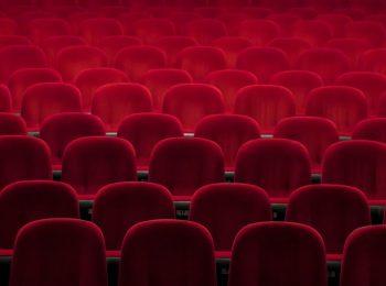 Blick in die leeren Stuhlreihen eines Kinos oder Theaters; die Stühle sind mit rotem Samt bezogen