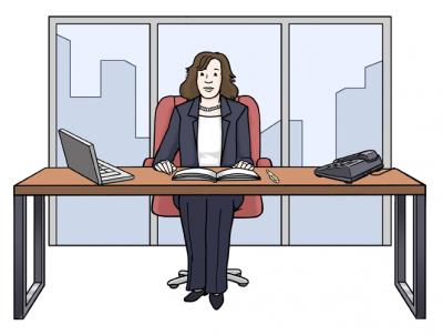 Eine Frau im Hosenanzug an einem Schreibtisch in Büro.