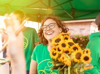 Grüne Mitglieder am Wahlkampf-Stand. Im Mittelpunkt des Bildes eine lachende junge Frau, die einen Strauß Sonnenblumen hält