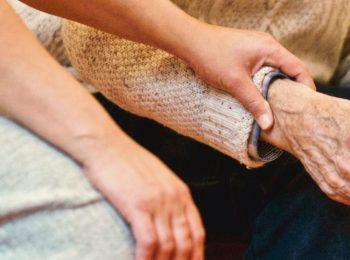 Ein junger Mensch legt seine Hand auf das Handgelenk eines alten Menschen