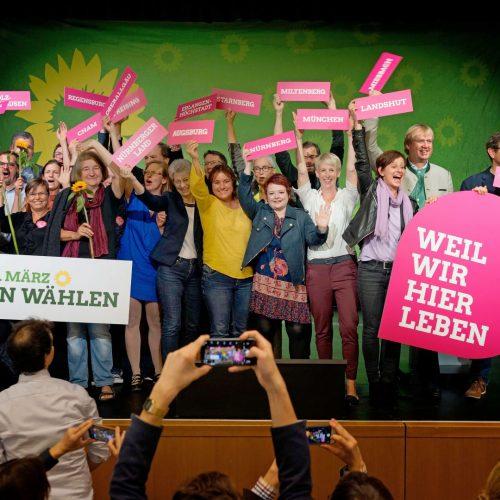 """Zur Kommunalwahl 2020 in Bayern treten so viele grüne Kandidat*innen wir noch nie an. Einige davon haben sich auf dem Landesparteitag in Lindau zum Gruppenfoto auf der Bühne versammelt. Sie halten Schilder mit den Aufschriften """"Weil wir hier leben"""" und """"Am 15. März grün wählen"""""""