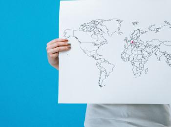 Internationale Solidarität ist für uns grüne ein zentrales Mittel, um die Coronakrise in den Griff zu bekommen. Das Beitragsbild steht symbolisch dafür: Eine Frau hält eine gezeichnete Weltkarte in Höhe, auf der Bayern pink markiert ist.