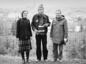 """1982: Drei junge Menschen stehen auf einem Hügel über Regensburg, mit einem kleinen Schild mit der Aufschrift """"WAA NEIN""""."""