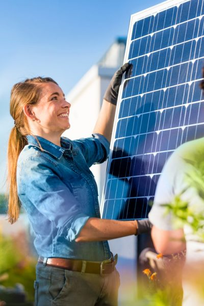 Eine Frau und ein Mann installieren ein Solar-Panel