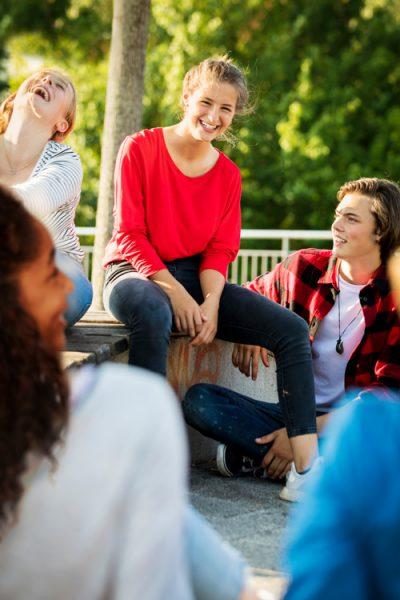 Eine Gruppe junger Menschen sitzt zusammen und lachen gemeinsam