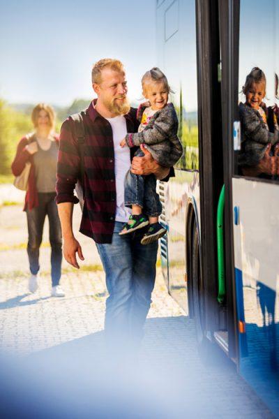 Ein Mann steigt mit seiner kleinen Tochter auf dem Arm in einen Bus des öffentlichen Nahverkehrs ein