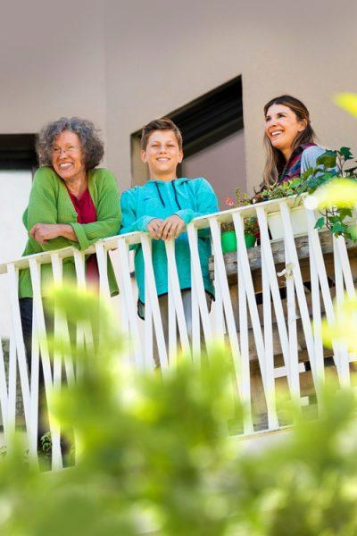 Eine ältere Dame, ein Junge und eine Frau stehen auf einem Balkon