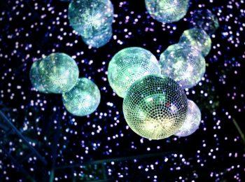 Zahlreiche glitzernde Discokugeln hängen von der Decke einer Kulturlocation und werfen viele kleine Lichtpunkte in den dunklen Raum