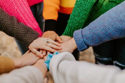 Ein Bild aus Vor-Corona-Zeiten: 8 Mitglieder eines Teams stehen im Kreis zusammen, Nahaufnahme ihrer aufeinander liegenden Hände