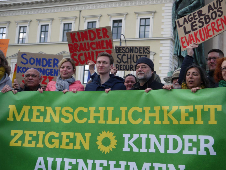 """Die Abgeordneten Cemal Bozoğlu, Katharina Schulze, Florian Siekmann, Gülseren Demirel, Margarete Bause sowie der Landesvorsitzende Eike Hallitzky halten ein Banner auf dem steht: """"Menschlichkeit zeigen, Kinder aufnehmen"""""""