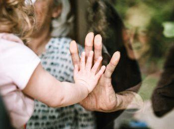 Nähe in Corona-Zeiten: Ein Kind und eine ältere Person, zwischen ihnen eine Fensterscheibe. Sie legen die Hände aufeinander.