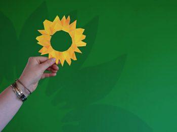 Eine ausgeschnittene Sonnenblume in Pixel-Optik wird von einer Hand vor einen grünen Hintergrund gehalten