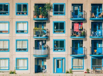 Fassade eines Mehrfamilienhauses mit hübschen blauen Fenstern und bepflanzten Balkonen.