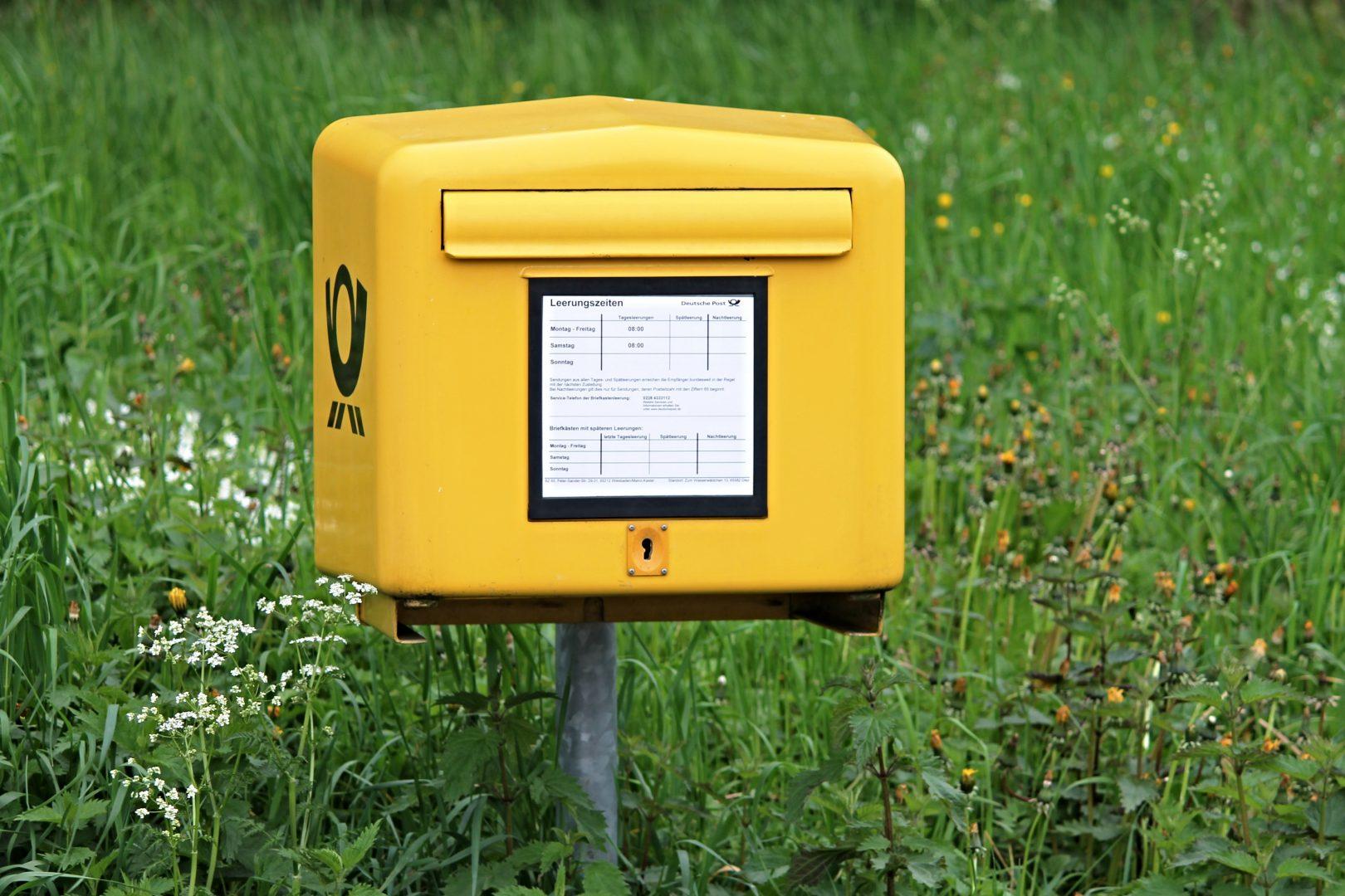 Ein gelber Briefkasten in einer grünen Wiese