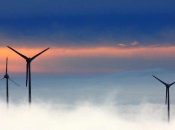 Stimmungsvolles Bild von Windrädern im Abendlicht, im Vordergrund steigt Nebel auf